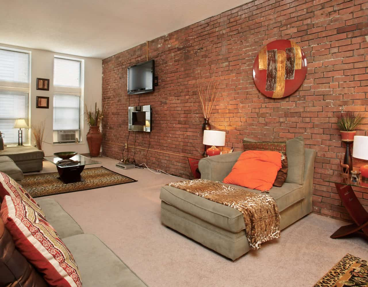 Full wall of exposed brick from the original Yale Brewery creates a beautiful accent to this apartment's charm